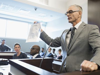 A grey-haired gentleman lawyer stands at the podium in a court room and holds up a document marked