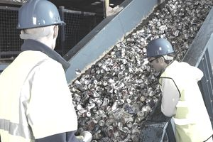 Workers at a recycling facility inspecting aluminum can bin