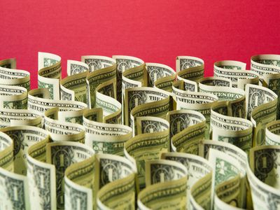 may dollar bills in front of a red background