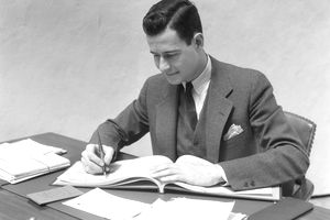 1930s-era man at a desk in an office writing in a business checkbook