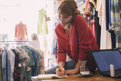 woman sitting on desk at clothing store on the phone, while writing something down