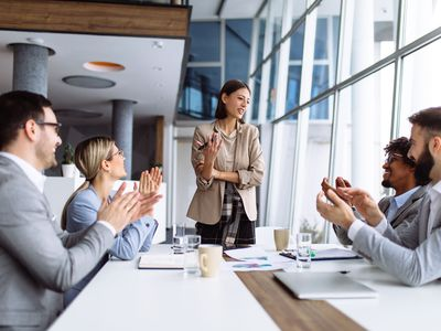Staff of Four Around an Office Table Applauding Female Boss Standing Up