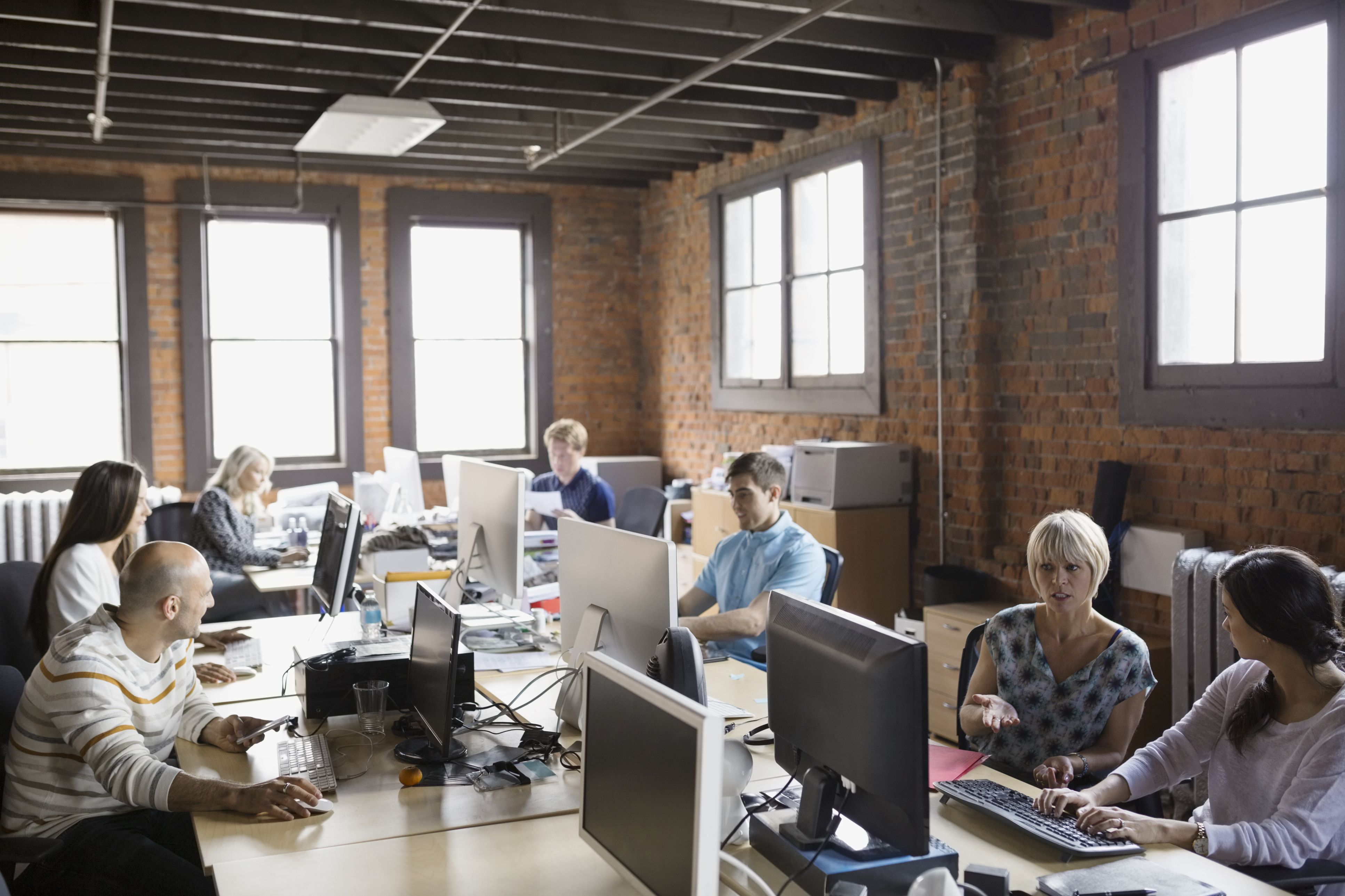 Business people working at computer workstations in office