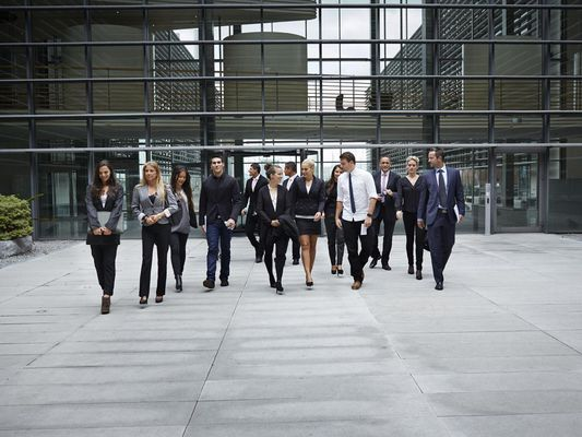 Big group of business people walking from building