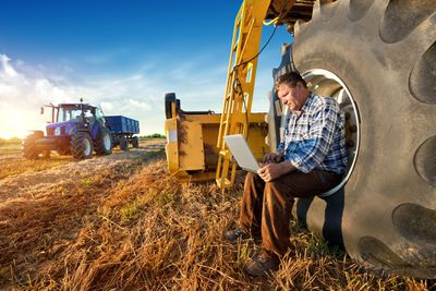 Farmer with equipment counting yields on a computer