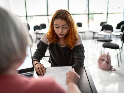 Woman helping girl with new hire forms