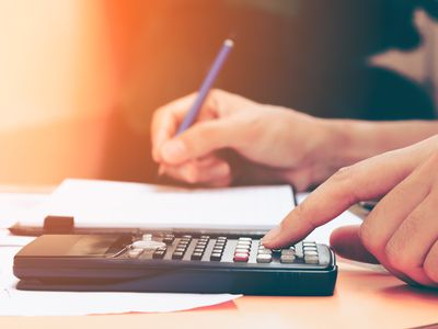 Close up woman using calculator and taking notes