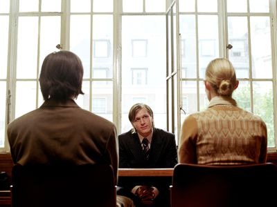 Couple at an arbitration meeting across table from an arbitrator
