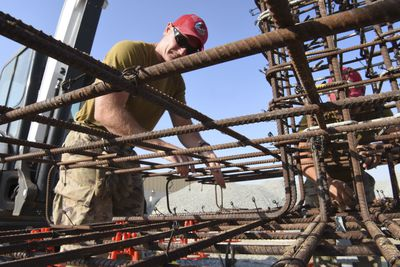 Tech. Sgt. Tracee Crane, 557th Expeditionary Rapid Engineer Deployable Heavy Operational Repair Squadron, Engineering pavement and equipment operator, places concrete chairs onto rebar during construction of Air Field Damage repair equipment warehouse, Dec. 23, 2018 at Al Dhafra Air Base, United Arab Emirates.
