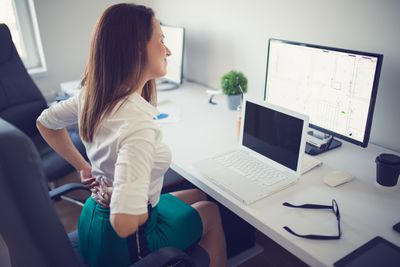 Woman sitting at desk in office chair holding her lower back in pain