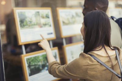 Young couple browsing real estate listings at storefront