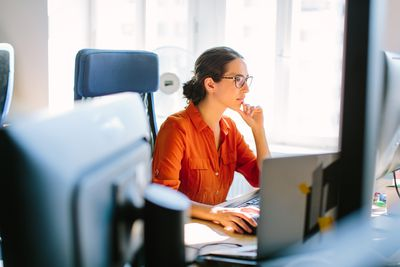 Business woman working at her desk, looking at a computer monitor