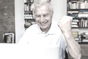 older man on laptop smiling and shaking his fist in victory