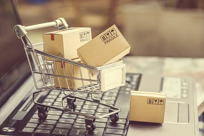 miniture shipping boxes in a shopping cart on a laptop keyboard