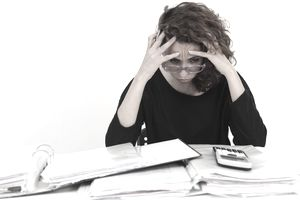 Frustrated woman sitting at table with binders full of tax information and a calculator.