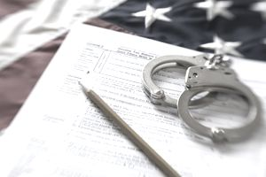Tax forms on top of an American flag with handcuffs, representing the legal trouble that can arise from tax evasion.