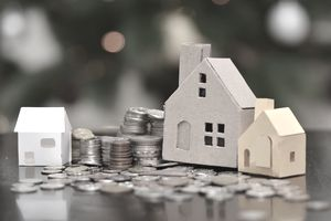 Close-Up Of Coins And Model Home