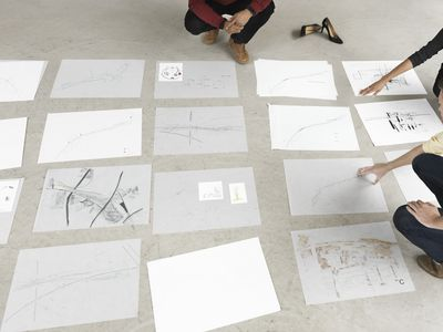 Start-up group creating a business plan portfolio by laying papers on the floor.to determine the flow.