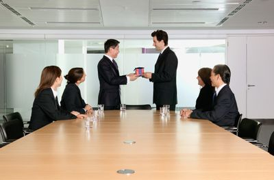 Employee presenting gift to boss in conference room with 4 other employees sitting at the table