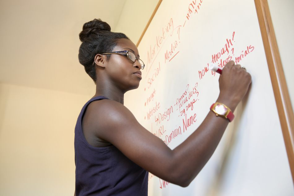 Young Black businesswoman uses white board to plan launch of new company.