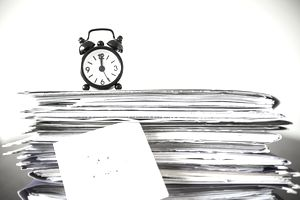 A pile of paper folders with a small clock sitting on top