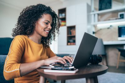 Young modern woman working from home, using laptop in quarantine
