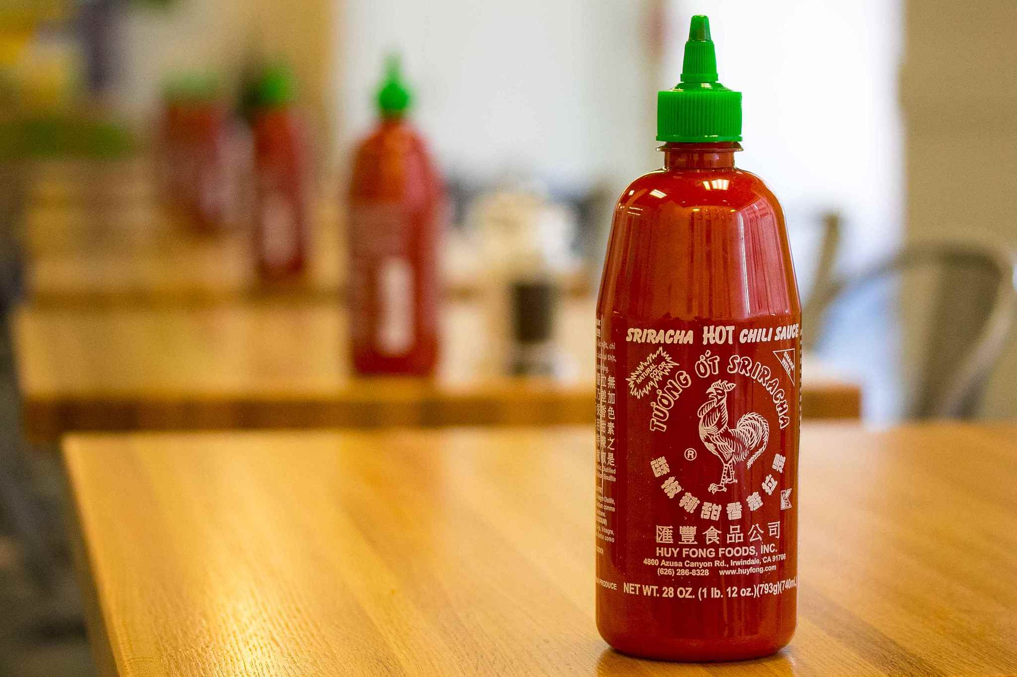 Restaurant tables lined with Sriracha sauce