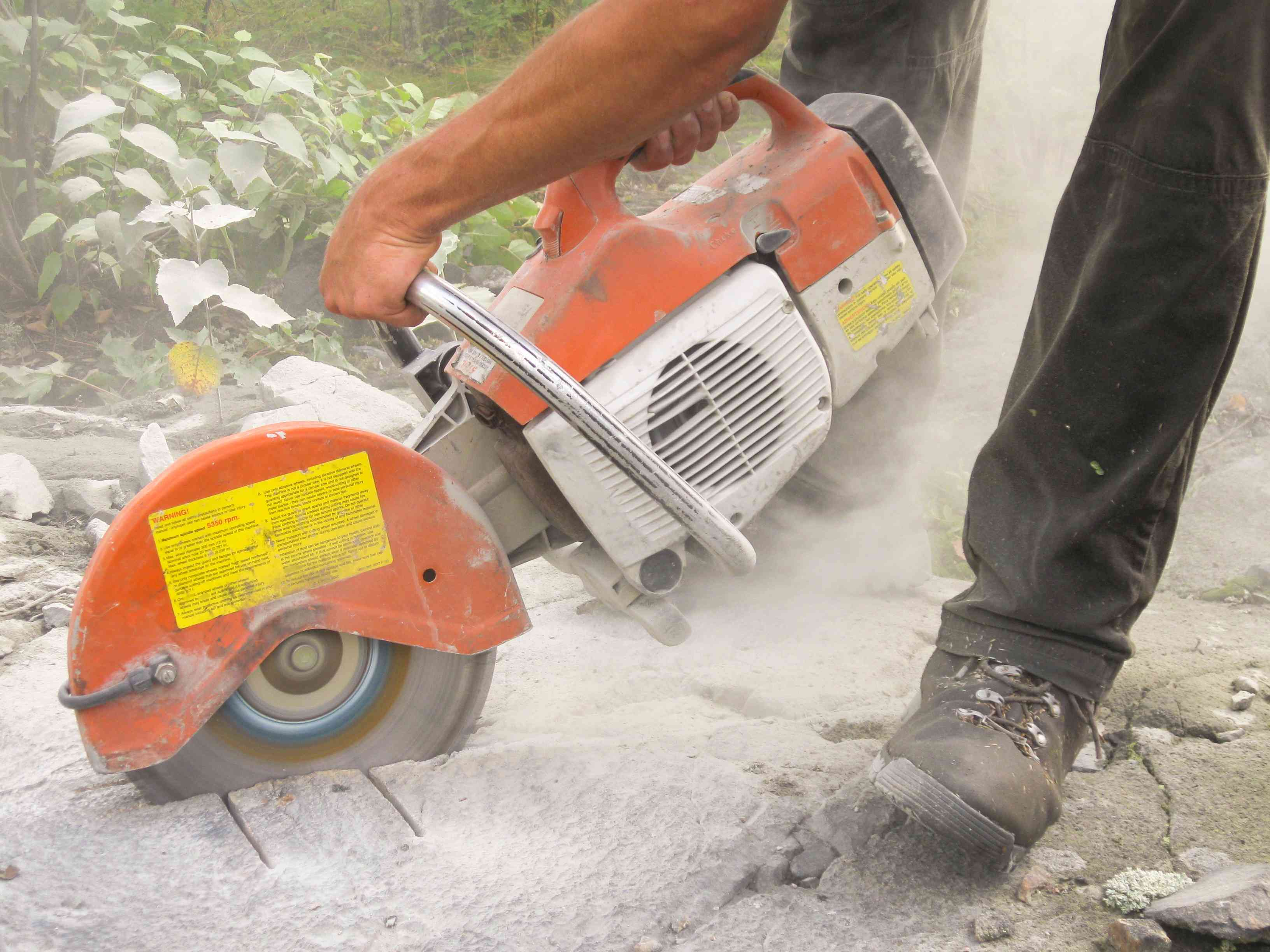 Man using groove cutter on concrete.