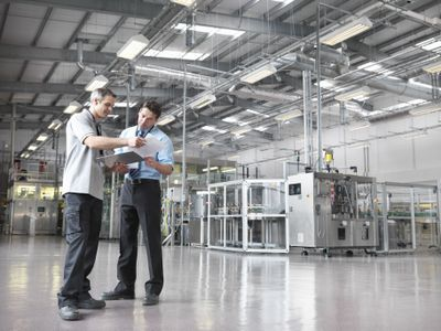 Two men looking at a clipboard in a warehouse