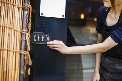 Close up of woman turning open sign on glass door to a bakery.