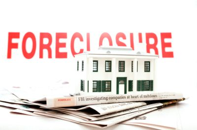 Foreclosure sign and newspaper with a model house.