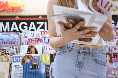 Young woman at bookstall with magazine, mid section