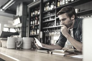 A bar owner looks concerned as he reviews a wage garnishment order