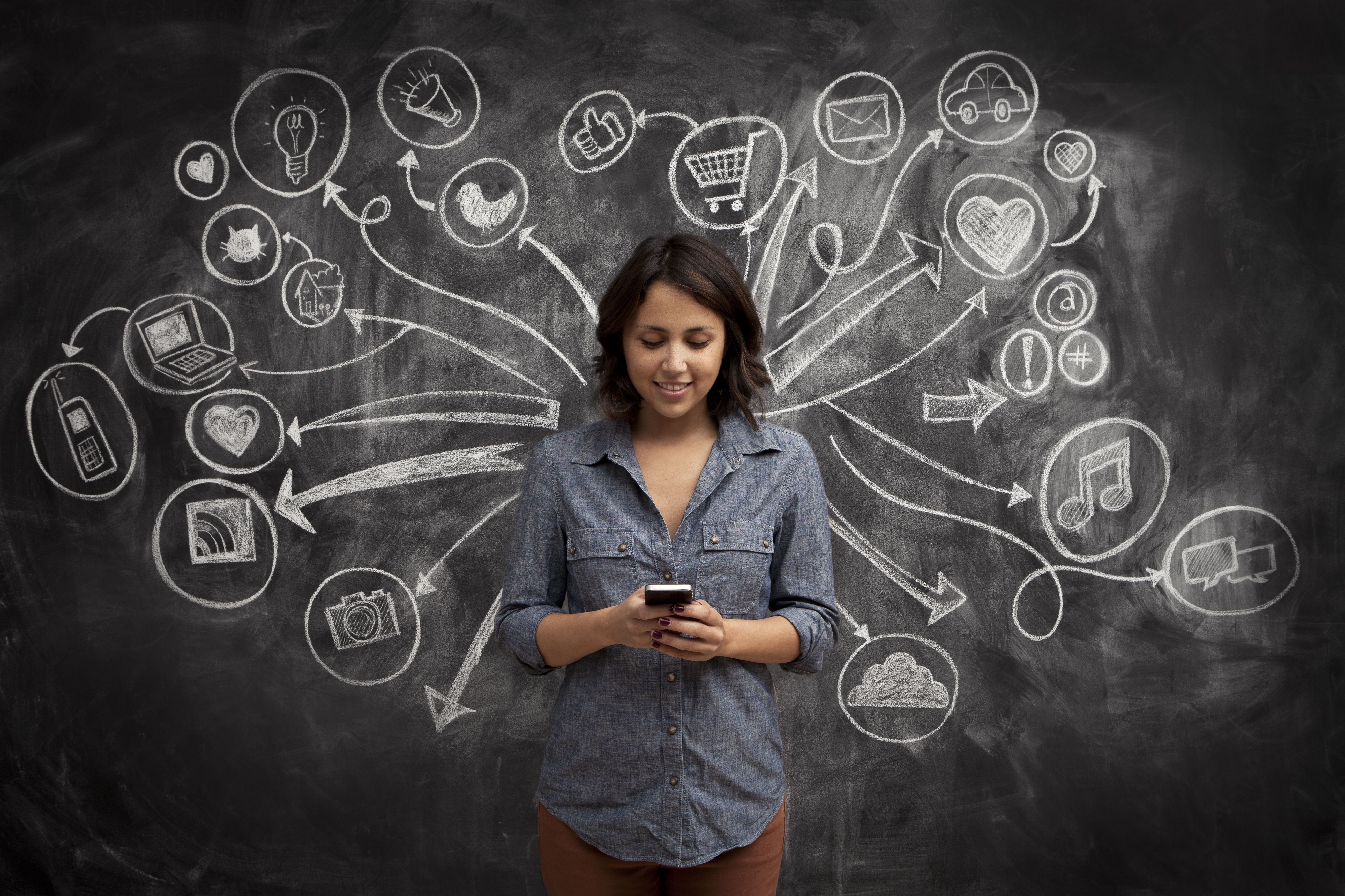 a young woman standing in front of a chalkboard with social media icons drawn