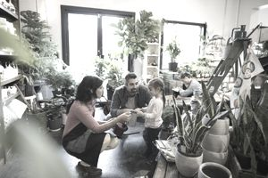 Female shop owner helping father and daughter shopping in plant shop