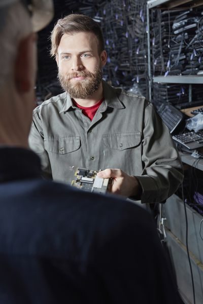 Man showing another man a piece of computer hardware