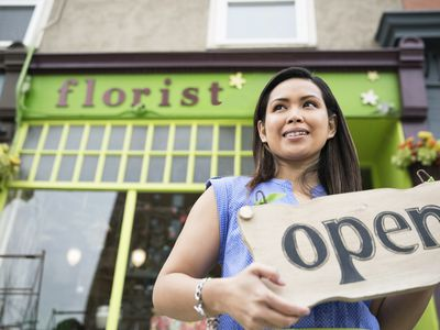 a woman standing in front of a flower shop holding an open sign