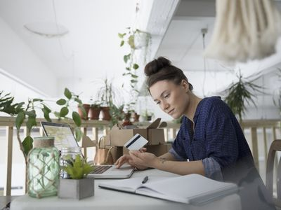 A young woman plant-shop owner sits at a light filled desk and scrutinizes her debit card.