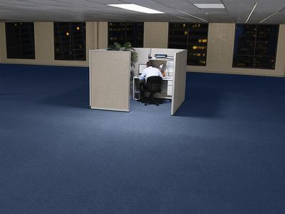 Businessman sitting at desk in cubicle in large empty room, high angle view, rear view
