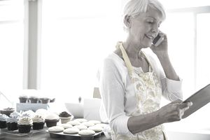Woman on cell phone baking cupcakes in kitchen