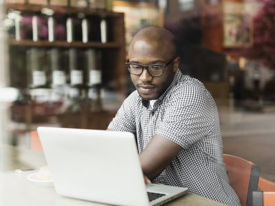 man using a laptop in coffee shop