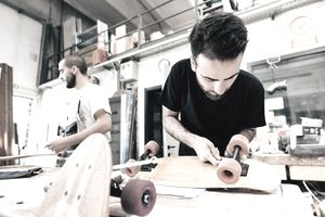 Young man in carpentry workshop attaching wheels to skateboard