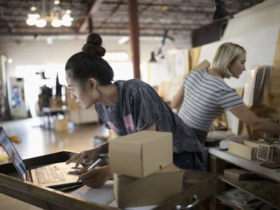 Female small business owner packaging merchandise at laptop in workshop