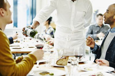 Waiter pouring wine for couples in restaurant