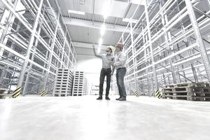 Two men planning operations in an empty warehouse