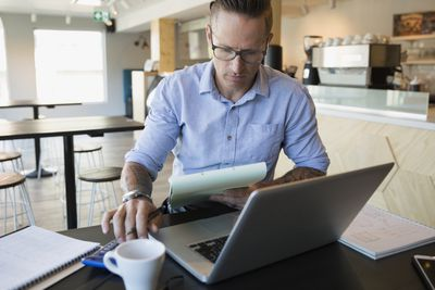 Male cafe owner paying bills with clipboard and calculator at laptop