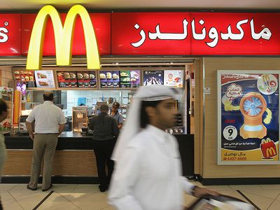 A man wearing traditional local clothes carries a tray of food from a McDonald's fast food restaurant in the City Center shopping mall in West Bay district on October 24, 2010 in Doha, Qatar.