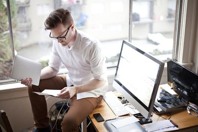 Freelancer sitting on a home desk reviewing paperwork and holding a tablet.