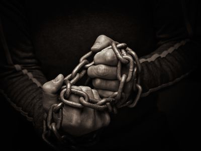 Close-up of hands trying to break chains