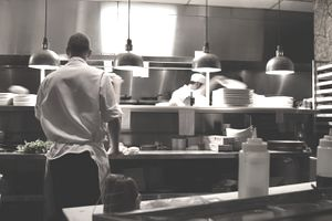 Line cooks working in a busy restaurant kitchen.